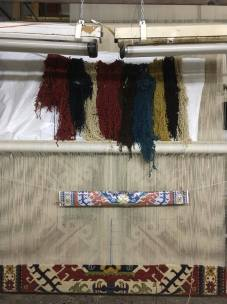 Dyed wool hanging above the template and a partially finished rug.